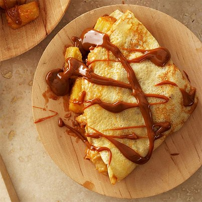 Breakfast of banana crepe drizzled with creamy chocolate caramel is sure to add immense happiness to your day. Oh yes, it will!