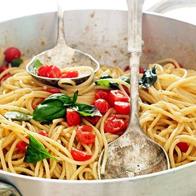 Spaghetti Aglio Olio with tomatoes and basil. This is fresh and pure Italian food at its best.
