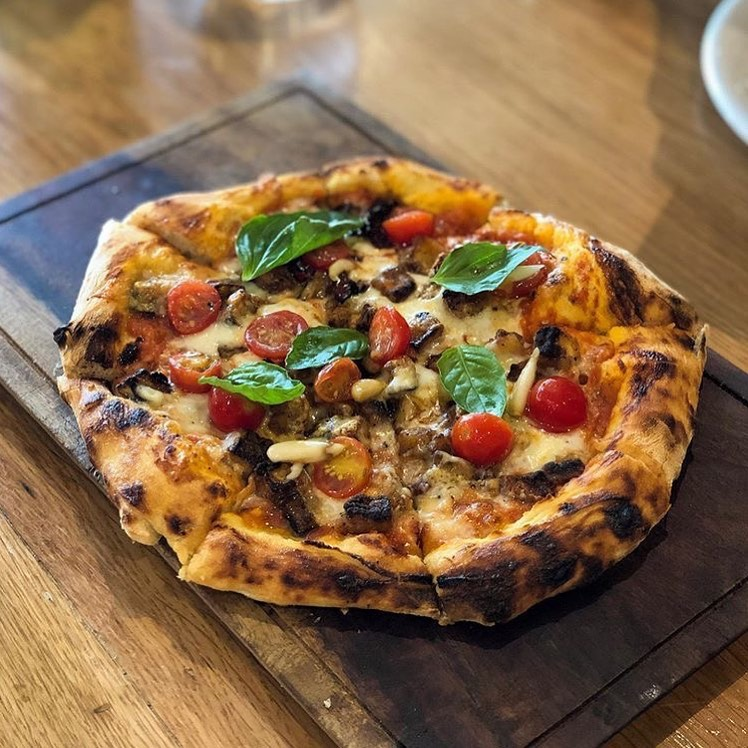 Introducing the Melanzana Parmigiana Pizza at @sorrentinabyfoodhall! Topped with eggplant, cherry tomatoes, and just the right layer of cheese, it's the perfect treat for all you #EggplantParm lovers out there. Just be sure to save room for a scoop (or three) of our freshly made gelato after. We can never say no to a cheeky combination of Chocolate (Cioccolato) and Strawberry Lemon (Limone alla Fragola)… it's the epitome of La Dolce Vita! #ForTheLoveofFood #SorrentinabyFoodhall #Gelato #HandChurned #TasteofItaly #GelatoLovers #IceCreamTime #MumbaiFoodie #TreatYourself